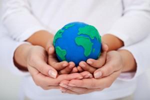 Manos de una mujer sostioenen las manos de un niño que sostienen al mundo