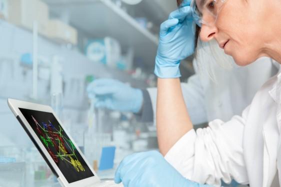 Investigador en un laboratorio observando pantalla con una molécula.