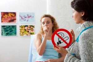 Doctora sosteniendo letrero de prohibido fumar al fondo una paciente acostada tosiendo