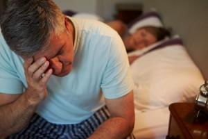 Hombre adulto levantandose de la cama en la noche