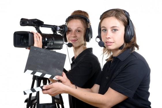Dos mujeres una sostiene una claqueta y la otra con cámara de video