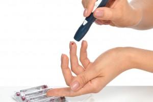 Acercamiento a las manos de una ujer que se mide la glucosa al lado insulina