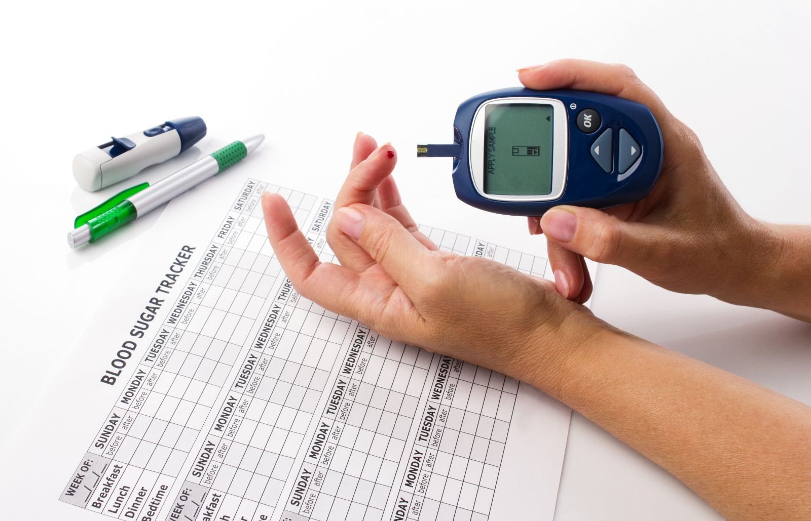 Acercamiento de mano de mujer midiéndose la glucosa y una hoja de bitácora de niveles de azúcar