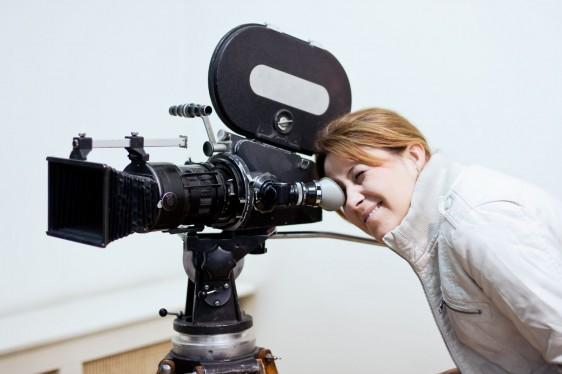Mujer observando en una cámara de ciine una escena