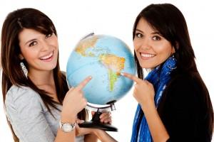 Dos mujeres sosteniendo flobo terraque apintando a América Latina