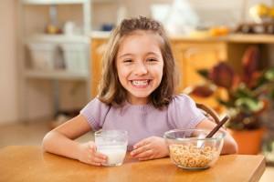 Niña sentada en mesa de madera tomado leche con cereal al lado