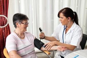Doctora con bauometro midiendo presió arterial de mujer adulta mayor