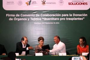 Jorge Lois Rodríguez, Mercedes Juan y José Eduardo Calzada Rovirosa sentados con otra persona firmando un documento