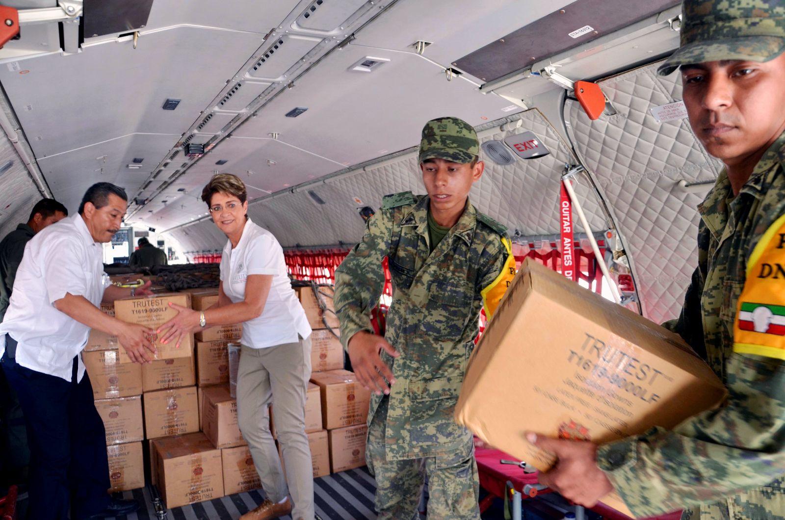Mercedes Juan y elementos de la Secretaría de la Defensa Nacional en un avión descargando medicmentos