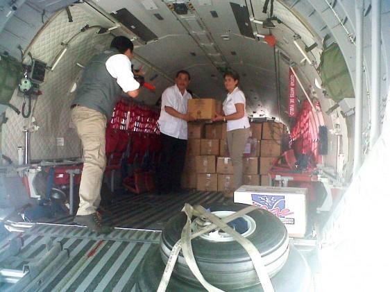 Mercedes Juan y dos personas descargando avión con medicamentos