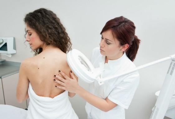 Deramtologa inspecciona la piel de una paciente.