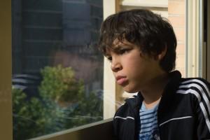 Niño en una ventana observando