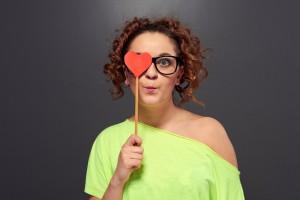 Mujer con gafas se cubre un ojo con recorte de corazón rojo