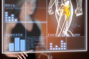 Pantalla de computadora mostrando cadera osea con el reflejo de una mujer al fondo