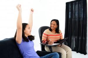 Mujer con los brazos arriba siendo escuchada por otra mujer que esscribe