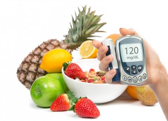 Persona sostiene glucómetro al fondo se observa un plato con fruta