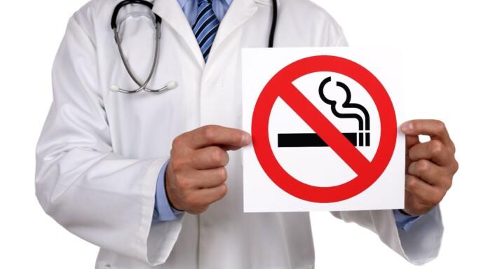Doctor con letrero que contiene ilustración de no fumar