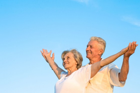 Pareja de adultos mayores on los brazos abiertos con un cielo azul