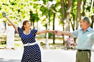 Dos adultos mayores bailando en un parque