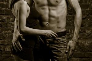 Mujer acariciando el cinturón de un hombre sin camisa
