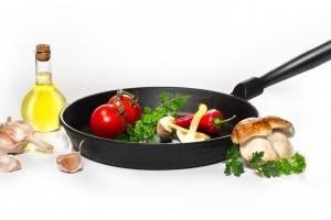 Aceite de oliva con verduras al lado de un sartén