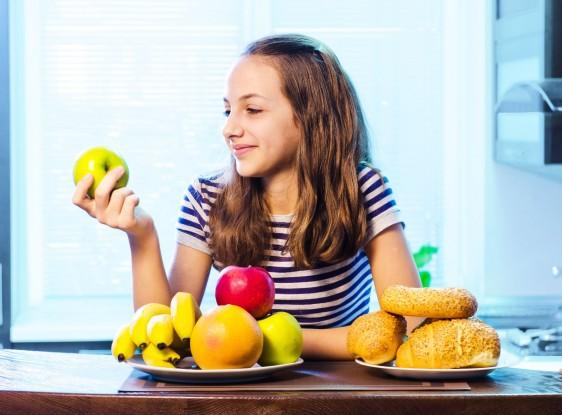 Niña seleccionando manzana versus un alimento con azúcar