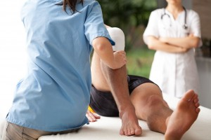 Una enfermera revisa una rodilla al fondo una doctora observa