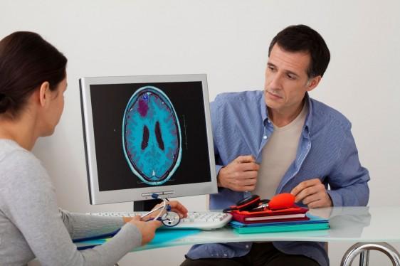 Doctora observa pantalla de cmputadora con imagen de cerebro al lado la acompaña un paciente