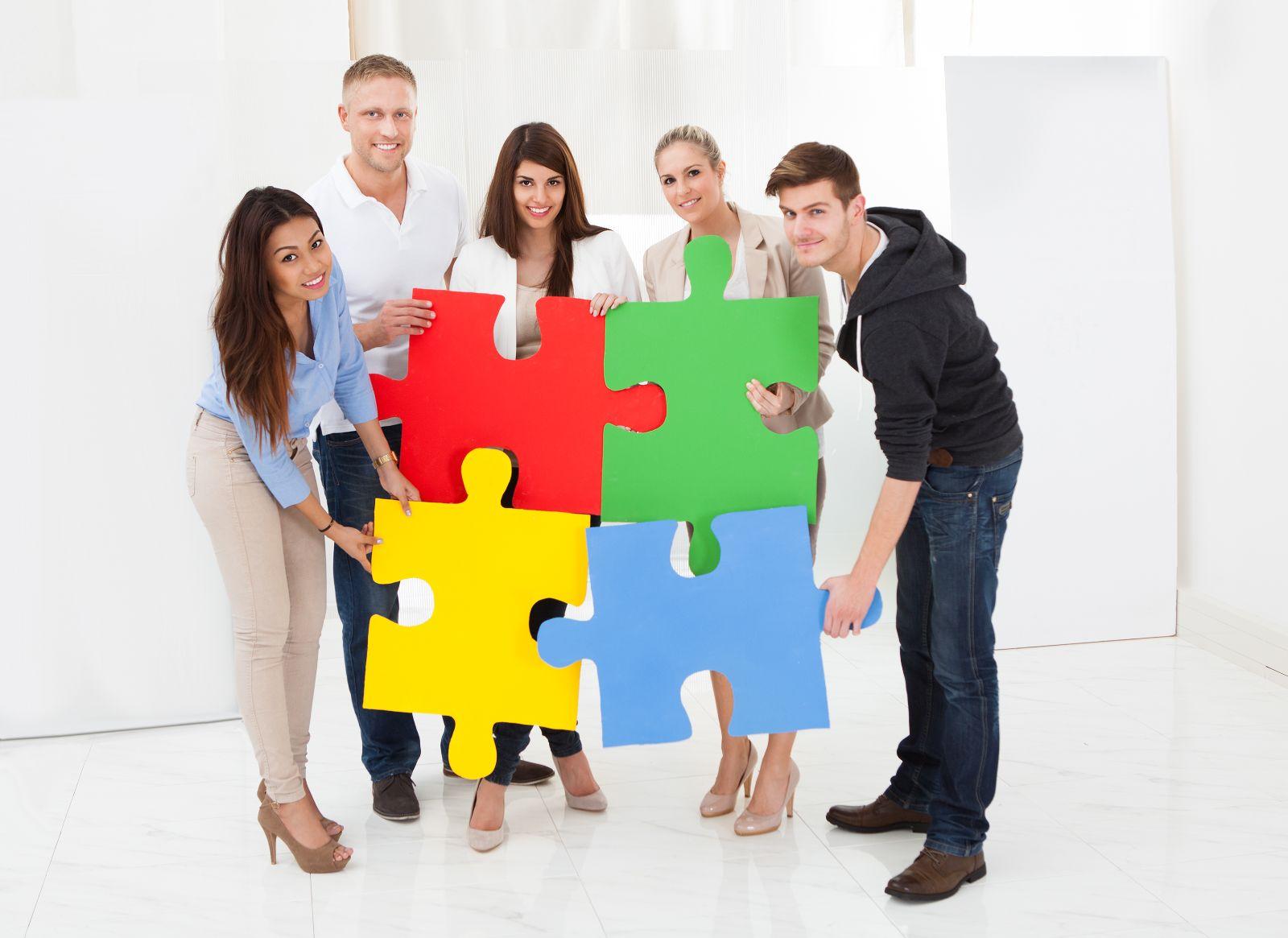Cinco personas de pie uniendo cuatro piezas de un rompecabezas