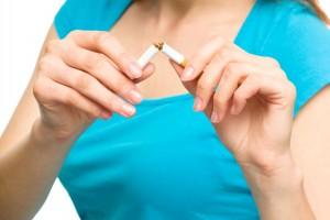 Acercamiento a las manos de una mujer que rompe un cigarro