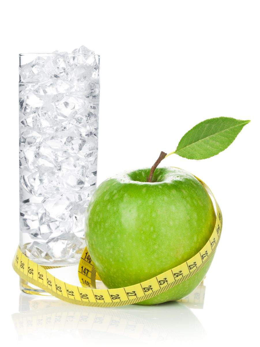 Manzana verde con cinta métrica al lado de una bebida gaseosa