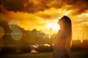 Mujer observando al ciel al fono un sol anaranjado