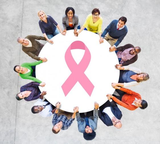 Mujeres alrededor de una malla de seguirdad circular con una ilustración del listón de cáncer de mama