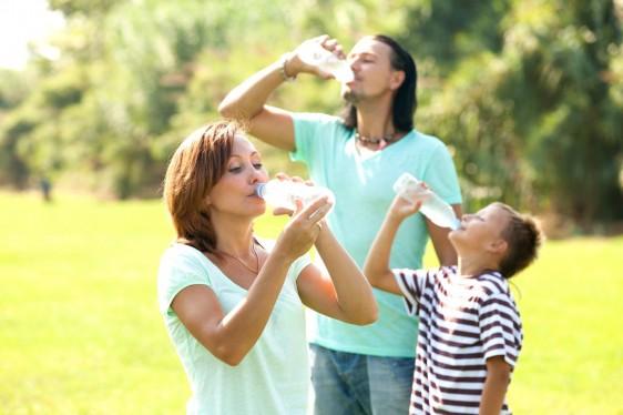 Familia tomando agua en un parque