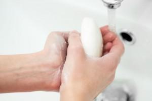 Acercamiento a las manos de una mujer lavándose las manos con agua y jabón