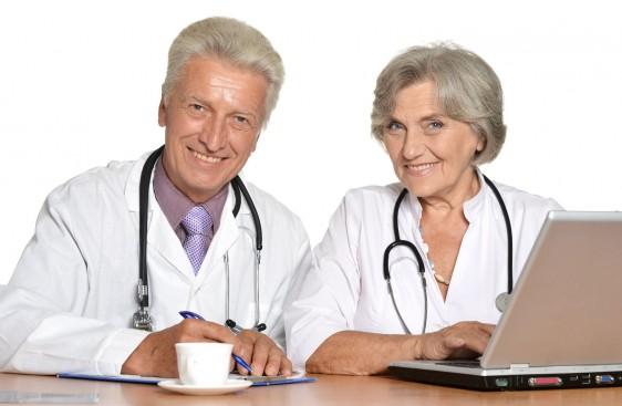 Par de médicos adultos mayores trabajando en una mesa