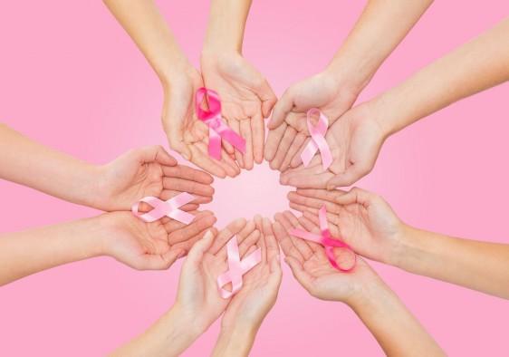 Acercamiento a manos de mujeres que sostienen listónes rosa