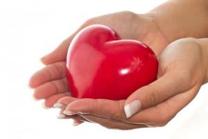Acercamiento a manos de una mujer que sostiene una figura en forma de corazón