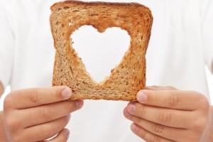 Acercamiento a las manos de un chef soteniendo un pan con recorte interno en forma de corazón