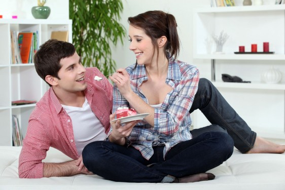 couple eating cake in bed