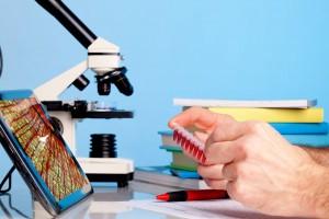 Acercamiento a manos que sistienen muestras de sangre al fondo un microscopio