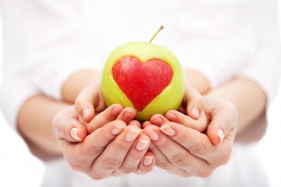 Acercamiento a las manos de una mujer que sostiene las manos con las palmas arriba de un niño que sostiene una manzana verde que contiene un corazón rojo