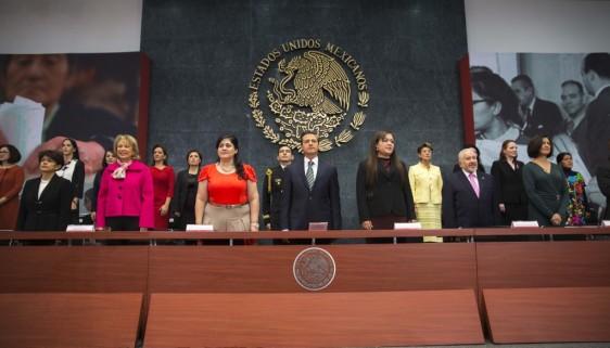 Funcionarios de pie al fondo el escudo nacional de los Estados Unidos Mexicanos