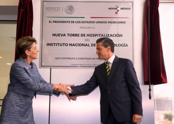 A la derecha Mercedes Juan a la izquierda Enrique Peña NIeto se dan la mano atras la placa conmemorativa de la inaguración