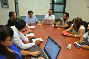 Funcionarios en junta de trabajo sentados en mesa