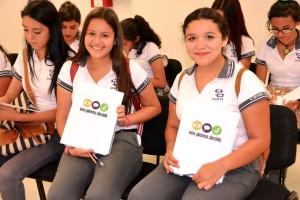 """Dos adolescentes mostrando una folder con el logotipo de la campaña """"Veo, Pienso, Decido"""""""
