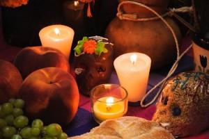 Ofrenda del día de muertos, pan de muertos, uvas, velas, amaranto calaveras y flores en el fondo