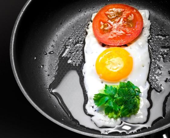 Huevos fritos con tomate y perejil en forma de semáforo en una sartén con aceite