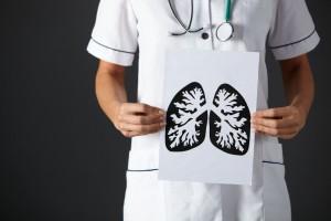 Enfermera mantiene hoja con diujo de pulmones a tinta