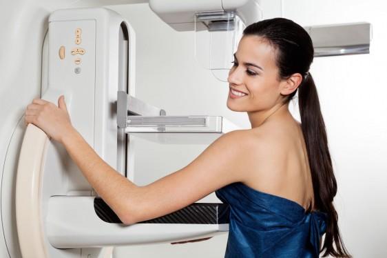 Mujer de pie en aparato de diagnóstico por imagen de mama